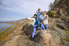 Happy family sitting on the stone and showing thumb Royalty Free Stock Images