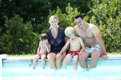 Happy family sitting by the swimming pool Stock Photo