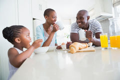 Happy family sitting and taking breakfast Stock Images