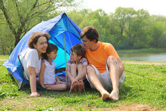 Happy family sitting in tent on lawn Royalty Free Stock Photos
