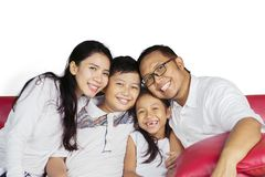 Happy family sitting together on the couch Stock Photo