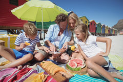 Happy family sitting together by fruits on blanket at beach Stock Images