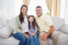 Happy family sitting together on sofa stock image