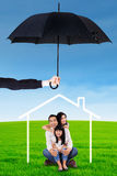 Happy family sitting under house icon and umbrella Stock Photo