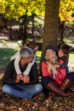 Happy family sitting under tree at park Royalty Free Stock Photography