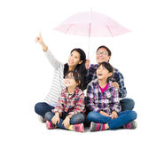 Happy family sitting under an umbrella Royalty Free Stock Photo