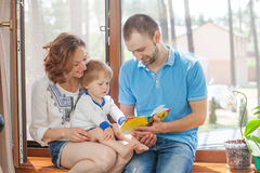 Happy family sitting on a windowsill Royalty Free Stock Photos