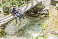Happy family are sitting on a wooden bridge in the middle of forest stock photography