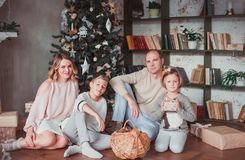 Happy family sitting on the wooden floor in the room next to the Christmas tree. They laugh. On the floor are cones. Warm colour stock photo