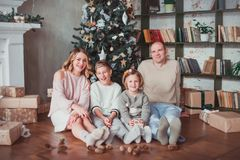 Happy family sitting on the wooden floor in the room next to the Christmas tree. They laugh. On the floor are cones. Warm colour stock image