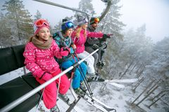 Happy family skiers on ski lift at mountain Stock Images