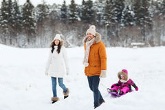 Happy family with sled walking in winter forest Stock Images