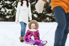 Happy family with sled walking in winter forest Stock Image
