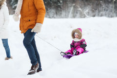 Happy family with sled walking in winter forest Royalty Free Stock Photography