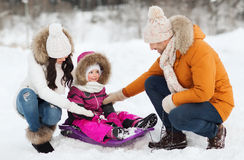 Happy family with sled walking in winter forest Royalty Free Stock Photo