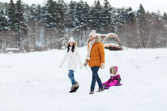 Happy family with sled walking in winter forest Royalty Free Stock Photos
