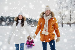 Happy family with sled walking in winter outdoors. Parenthood, fashion, season and people concept - happy family with child on sled walking in winter outdoors Royalty Free Stock Photos