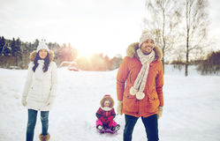 Happy family with sled walking in winter outdoors. Parenthood, fashion, season and people concept - happy family with child on sled walking in winter outdoors Royalty Free Stock Photography