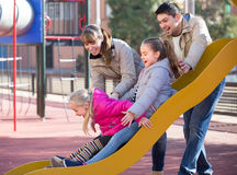 Happy family at sliding board outdoors Royalty Free Stock Images