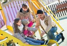 Happy family at sliding board outdoors Stock Photos