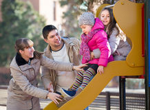 Happy family at sliding board outdoors Royalty Free Stock Image
