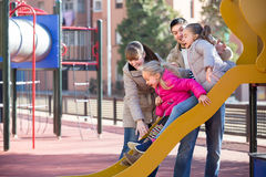 Happy family at sliding board outdoors Stock Photo