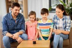 Happy family with smart speaker at home. Family, technology and internet of things concept - happy father, mother, little son and daughter with smart speaker at stock photography