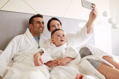 Happy family with smartphone in bed at hotel room Stock Image