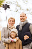 Happy family with smartphone and monopod in park Royalty Free Stock Photography