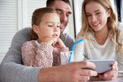 Happy family with smartphone at restaurant Royalty Free Stock Image