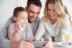 Happy family with smartphone at restaurant Stock Photography