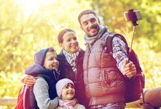 Happy family with smartphone selfie stick at camp Royalty Free Stock Photography