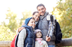 Happy family with smartphone selfie stick in woods Royalty Free Stock Images