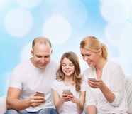 Happy family with smartphones. Family, holidays, technology and people - smiling mother, father and little girl with smartphones over blue lights background Stock Photos