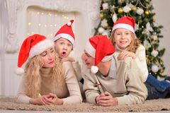 Happy family celebrating New Year Christmas. The happy family smile, lie on the floor, celebrating New Year Christmas Royalty Free Stock Photography