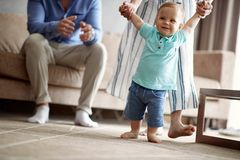 Happy family -Smiling baby boy making first steps. At home royalty free stock photography