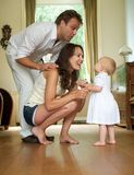 Happy family smiling at baby standing at home Royalty Free Stock Photos