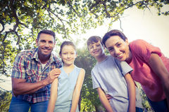 Happy family smiling at camera in the park Royalty Free Stock Images