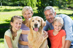 Happy family smiling at the camera with their dog Stock Image