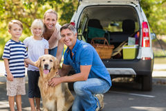 Happy family smiling at the camera with their dog Royalty Free Stock Photography