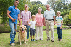 Happy family smiling at the camera with their dog Royalty Free Stock Images