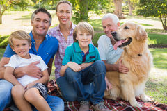Happy family smiling at the camera with their dog Stock Images