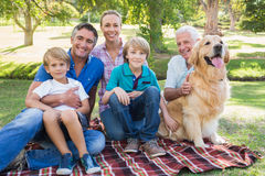 Happy family smiling at the camera with their dog Stock Photo