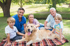 Happy family smiling at the camera with their dog Royalty Free Stock Photos