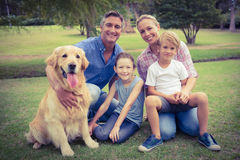 Happy family smiling at the camera with their dog Stock Photography