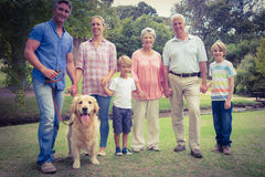 Happy family smiling at the camera with their dog Royalty Free Stock Image