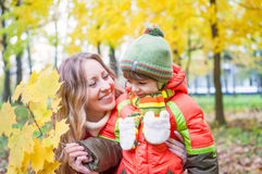 Happy family smiling and holding autumn leaves Royalty Free Stock Photo