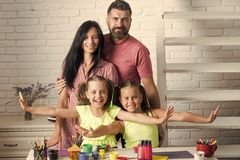 Happy family smiling at table with colorful paints. Markers and pencils. Love and care concept. Childhood and parenting. Arts and crafts stock photography