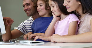 Happy family smiling and using a computer together. At home stock video footage