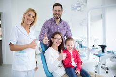 Happy family with a smiling young dentist royalty free stock images